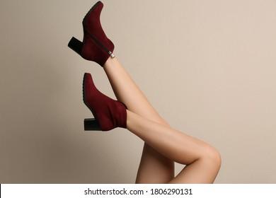 Woman wearing stylish boots on beige background, closeup - Shutterstock ID 1806290131