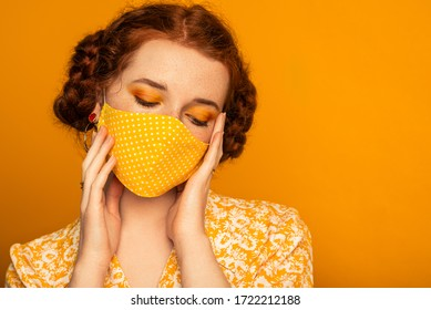Woman wearing stylish handmade protective face mask posing on orange background. Monochrome color outfit. Model with bold eyes makeup. Fashion during quarantine of coronavirus. Copy space for text