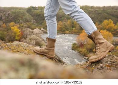 Woman wearing stylish hiking boots on steep cliff, closeup