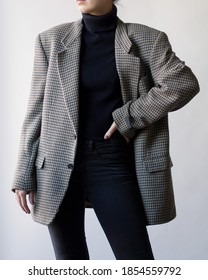 Woman wearing stylish outfit with black turtleneck, oversized check blazer and black jeans isolated on white background. Copy space