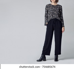 Woman wearing stylish outfit with black patterned blouse, black high-waisted wide leg trousers and black ankle boots isolated on grey background. Copy space