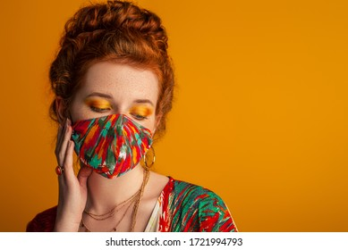 Woman wearing stylish outfit with designer protective bold colors face mask, matching eyes makeup, dress. Trendy Fashion accessory during quarantine of coronavirus pandemic. Copy, empty space for text