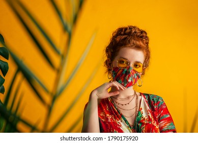 Woman wearing stylish outfit with designer protective bold colorful face mask, matching dress, yellow sunglasses, chain necklace. Trendy Fashion accessory during quarantine. Copy, empty space for text