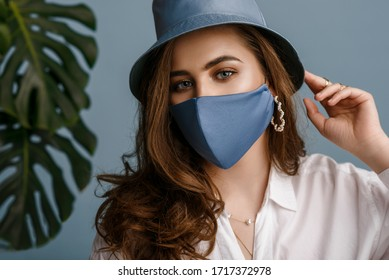Woman wearing stylish outfit with luxury designer protective blue face mask, bucket hat, pearl earrings. Trendy Fashion accessory during quarantine of coronavirus pandemic. Close up studio portrait