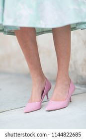 Woman wearing stylish pink high-heeled formal court shoes and a green dress standing against an exterior wall in a low angle view of her feet