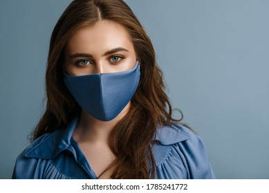 Woman wearing stylish protective blue face mask. Young beautiful brunette model. Trendy Fashion accessory during quarantine of coronavirus pandemic. Close up studio portrait. Copy, empty space