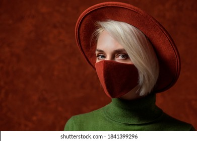 Woman wearing stylish protective cloth face mask, posing on orange background. Trendy autumn fashion accessory during quarantine of coronavirus pandemic. Close up portrait. Copy, empty space for text