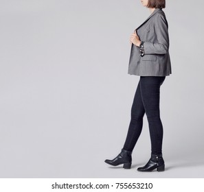 Woman wearing stylish and smart outfit with floral patterned blouse, gray elegant double-breasted blazer, black skinny jeans and black ankle boots isolated on gray background. Copy space