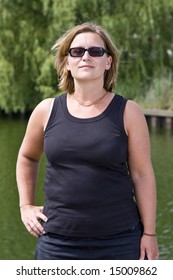 Woman wearing sunglasses with a happy, confident expression