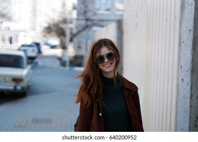 Woman wearing sunglasses on the street on the background of cars