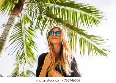 woman wearing sunglasses posing with palm tree