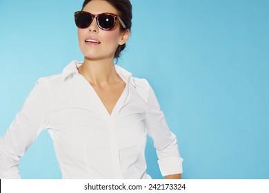Woman wearing sunglasses and white shirt.