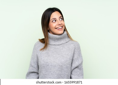 Woman wearing a sweater over isolated green background laughing and looking up