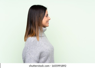 Woman wearing a sweater over isolated green background looking to the side