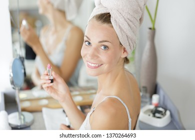woman wearing towel turban and holding lipstick
