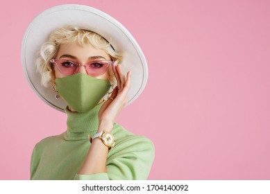 Woman wearing trendy fashion outfit during quarantine of coronavirus outbreak. Model dressed protective stylish handmade face mask, pink sunglasses, white hat, wrist watch, green mint color turtleneck - Shutterstock ID 1704140092