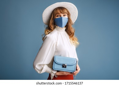 Woman wearing trendy spring, summer fashion outfit during quarantine of coronavirus outbreak. Model dressed protective stylish handmade face mask, hat, holding small blue bag. Copy, empty space