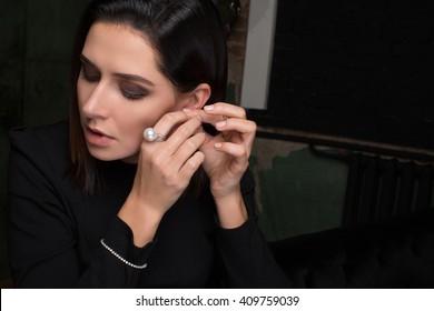 Woman wearing, tries on earring