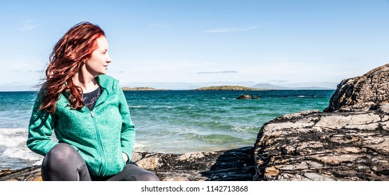 Woman wearing a turquoise hoodie with red hair sitting on some rocks with beach and ocean in the background. Taken on Renvyle beach, along the Wild Atlantic Way in Ireland in summer.