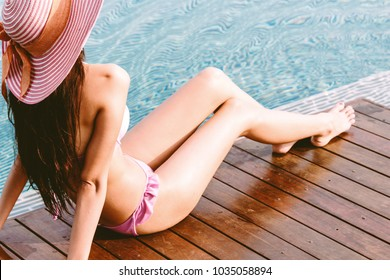 Woman wearing two piece bikini in swimming pool on summer vacation relaxing at resort spa