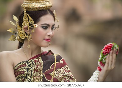 woman wearing typical thai dress with thai style temple background, identity culture of thailand