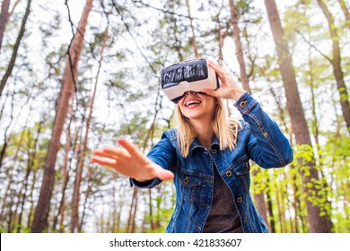 Woman wearing virtual reality goggles outside in spring nature. VR glasses. 360 degrees. Virtual reality headset. VR game. Wearing virtual reality goggles. Smartphone with VR. Virtual reality video.