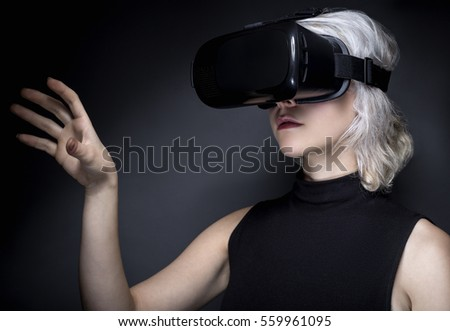 Woman wearing a virtual reality headset touching or holding something.  She is interacting with something she is watching or playing a video game.  The image depicts VR and AR technology.