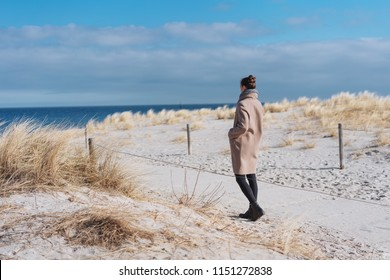 Woman wearing a warm overcoat and scarf walking through sand dunes to the sea on a cold sunny winter day