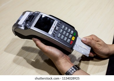 Woman wearing watch inserting and swiping chip credit card/debit card into EDC card reader terminal on wood table background