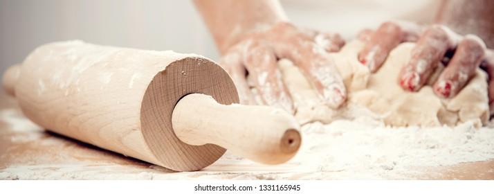 Woman wearing white apron kneading dough using rolling pin close-up female hands making cooking baking cakes pies flour on table. Cook at work or housewife in the kitchen horizontal conceptual image