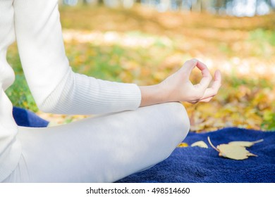 Woman wearing white clothes relaxing and practicing yoga in the park atmosphere, where sunlight plays with shadows. Focus point on the hand.