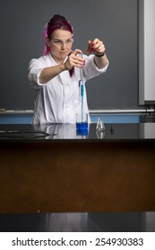 a woman wearing a white coat and safety glasses is doing an experiment in a school laboratory
