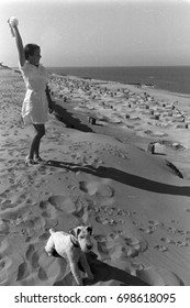 Woman wearing white dress and playing with dog on beach