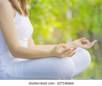 Woman wearing white dress, yoga and meditation pose ,green bokeh background,copy space.