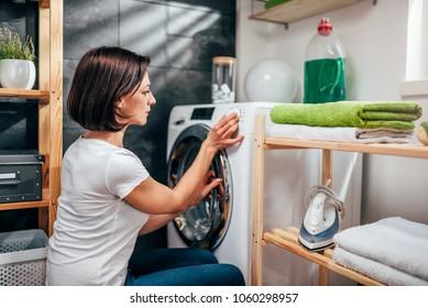 Woman wearing white shirt choosing program on washing machine in laundry room