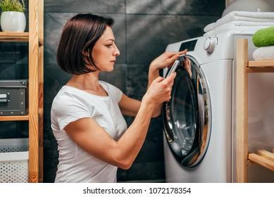 Woman wearing white shirt using smart phone to control washing machine at laundry room