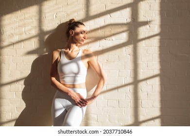 Woman wearing a white yoga outfit - Beautiful sportive woman leaning on a white brick wall