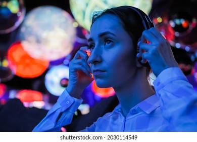 Woman wearing wireless black headphones and looking around in dark room of interactive exhibition or museum with colorful illumination. Futuristic, entertainment, immersive concept