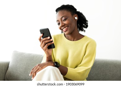 Woman wearing wireless earbuds and using a mobile phone