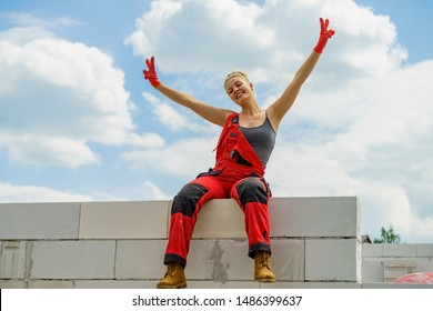 Woman wearing workwear on construction site. Female takes break from work, sitting on wall. Partially built new house early stage. Industry.