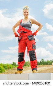 Woman wearing workwear on construction site. Female takes break from work, standing on wall against blue sky. Partially built new house early stage. Industry.