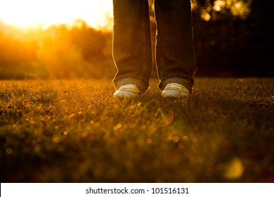 Woman wearing yellow basketball shoes with the suns rays shinning on ground.