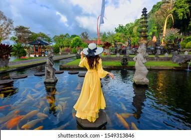 Woman wearing yellow dresses to feed koi fish in Taman Tirtagangga temple on Bali,Indonesia