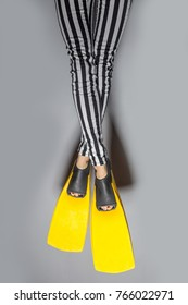 Woman wearing yellow flippers over gray background