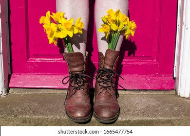 Woman wearing yellow flowers in brown boots against pink front door. Feminine quirky fun eye catching British England Spring Summer instagram style concept idea