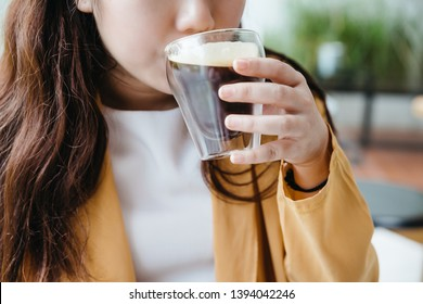 Woman wearing yellow jacket sipping Frothy Nitro Cold Brew Coffee in drinking glass with green blur background.