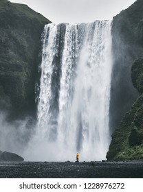 Woman wearing yellow raincoat enjoying scenic view to huge and powerful Skogafoss waterfall in South Iceland - travel, adventure and explore concept
