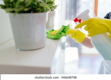 Woman wearing yellow rubber protective gloves and cleaning white shelf.