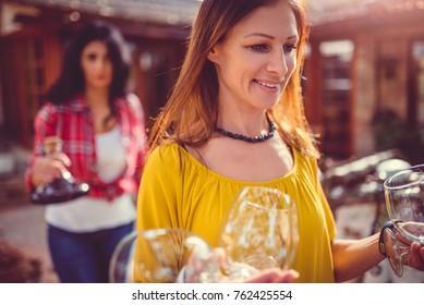 Woman wearing yellow shirt carrying wine glasses at backyard patio