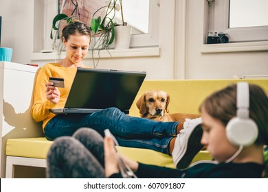 Woman wearing yellow sweater sitting on yellow sofa at home and shopping online with credit card.